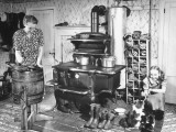 An Old Woman Working in the Old Fashioned Kitchen While the Young Girl Plays with Her Kitten
