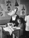 A Nun Looking over a Fashion Magazine with One of Her Dressmaking Students