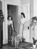 Two Women Talking in the Doorway of a Home  One Holding a Dog by a Leash