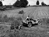 Farmer Using Jeep to Pull His Plow in Demonstration of Postwar Uses for Military Vehicles