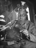 Comedian Ed Wynn Clowning as the King Bubbles Trying to Fix a Shoe