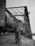A Guard Standing at the Railroad Bridge  Watching the Passing Freight Train