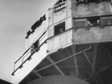 US Navy Personnel Peering Out of Openings in Section of Ship Called the Foretop