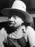 Farmer Wearing a Straw Hat  Glasses  Bib Overalls  and Smoking a Pipe