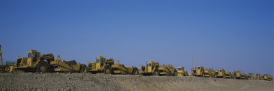 Row of Bulldozers at a Construction Site Stretched Canvas Print
