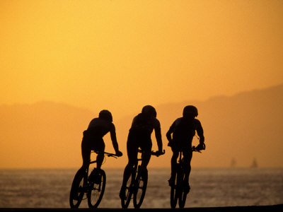 Silhouette of Three Men Riding on the Beach Stretched Canvas Print