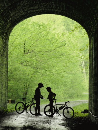 Two Silhouetted Cyclists Stop in a Tunnel on a Bike Trail Stretched Canvas Print