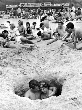 Couple Cuddling While Sitting in a Hole as Others Enjoy the Beach on the 4th of July Stretched Canvas Print
