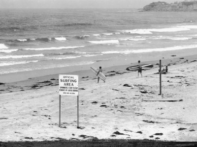"Surfers Walking to Water Behind Sign Reading ""Official Surfing Area"" Stretched Canvas Print"