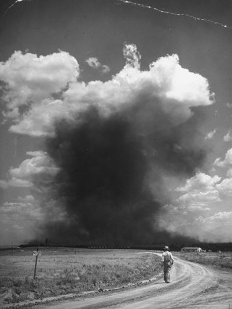 http://cache2.artprintimages.com/p/LRG/27/2702/LCDND00Z/art-print/alfred-eisenstaedt-man-walking-down-dirt-road-as-sky-fills-with-dark-clouds-from-a-carbon-black-plant.jpg