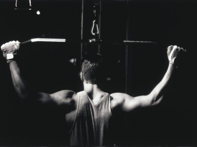 Rear View of a Young Man Exercise on a Lateral Pull-Down Weight Machine Stretched Canvas Print