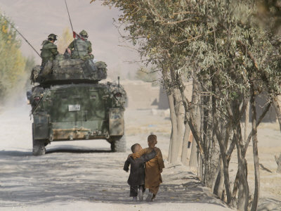 Afghan Boys Walk Along a Path While International Security Assistance Force (Isaf) Stretched Canvas Print