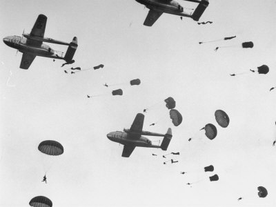 """Scores of Paratroopers Dropping from C-82 """"Flying Boxcar"""" and Landing on Level Ground Stretched Canvas Print"""