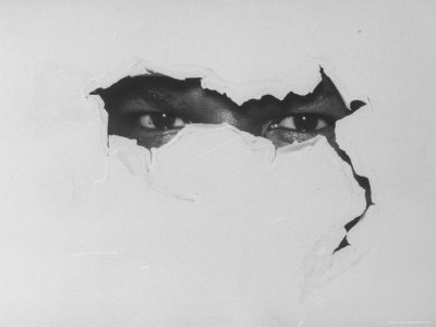African American Man's Eyes Peering Through Torn Paper Symbolizing Hard Core Black Extremists Stretched Canvas Print