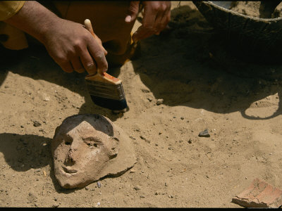An Archeologist Brushes Sand Away from a Ceramic Artifact Stretched Canvas Print