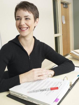 Smiling Teacher at Desk Stretched Canvas Print