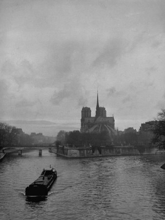 River Barge Churning up the Seine Past Notre Dame Cathedral on a Gloomy Winter Day Stretched Canvas Print
