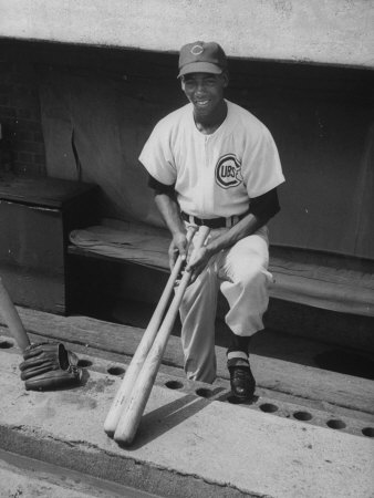Chicago Cub's Ernie Banks, Stooping in the Dug-Out Holding Two Bats Against Cincinnati Reds Stretched Canvas Print