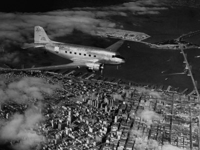Plane Flying over a City from a Story Concerning United Airlines Stretched Canvas Print