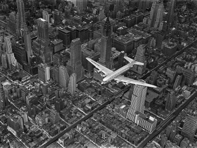 Aerial View of a Dc-4 Passenger Plane in Flight over Manhattan Stretched Canvas Print