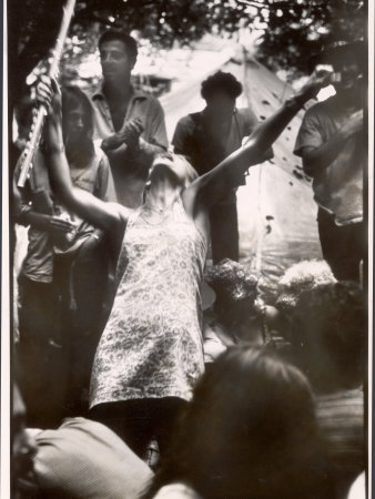 Hippie Girl Enthusiastically Playing Flute and Dancing at Woodstock Music Festival Stretched Canvas Print