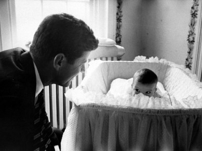Sen. John F. Kennedy Playing Peek-A-Boo with His Daughter Caroline in Her Crib Stretched Canvas Print