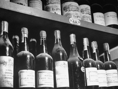 Dust-Covered Wine and Brandy Bottles Standing on Racks in a Wine Cellar Stretched Canvas Print