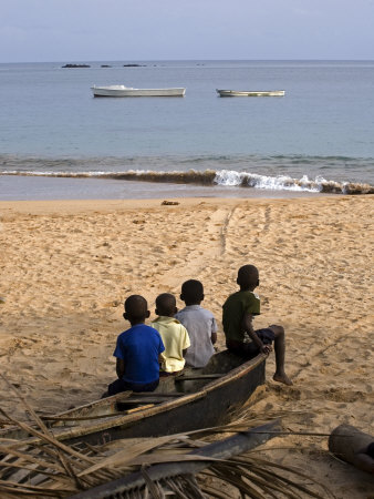 Four Small Boys Look Out to Sea from Where They Sit on Bamboo Fishing Boat on Island of Princip? Stretched Canvas Print