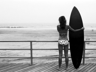 Model with Black Surfboard Standing on Boardwalk and Watching Wave on Beach Stretched Canvas Print