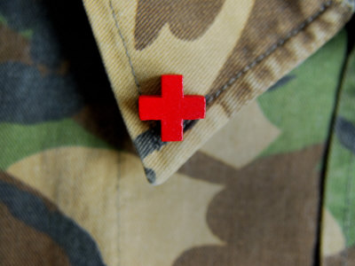 Red Cross on the Collar of a Camouflage Jacket Stretched Canvas Print