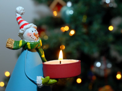 Close-Up of a Snow Man Candle in Front of a Tree with Christmas Lights Stretched Canvas Print