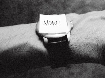 The Word Now as a Reminder Attached to a Watch on a Male Arm Stretched Canvas Print