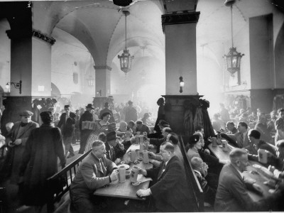The Hofbrauhaus with Patrons Sitting at Long Tables Holding Large Steins of Beer Stretched Canvas Print