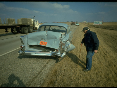 Man Inspecting Extensive Damage to Rear of His Car after Accident Stretched Canvas Print