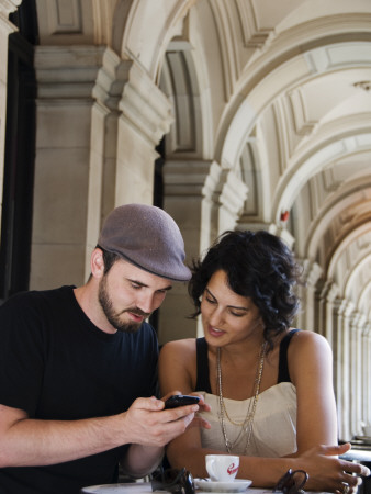 Couple at Cafe at Gpo Using Mobile Phone to Access Travel Information Stretched Canvas Print