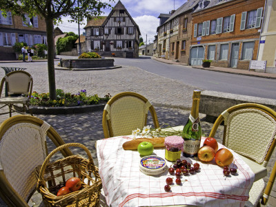 Cheese, Cherries, Apples and Champagne on Cafe Table with Half-Timbered House in Background Stretched Canvas Print