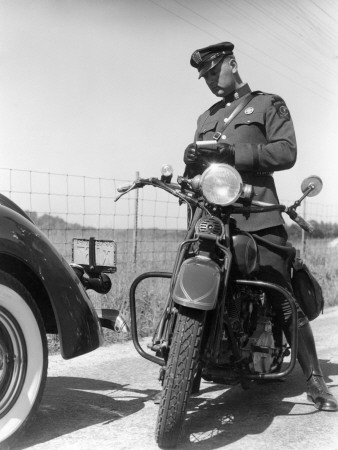 Policeman on a Motorcycle Writing a Ticket From Information on the Vehicles License Stretched Canvas Print