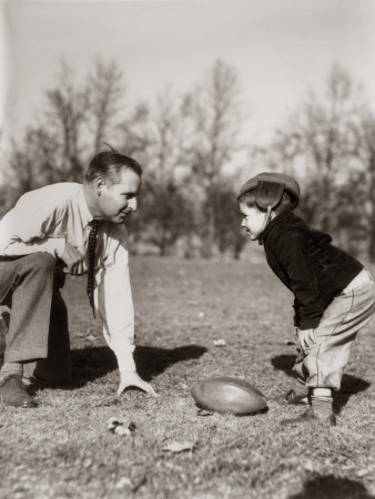 Father and Son Playing Football Stretched Canvas Print