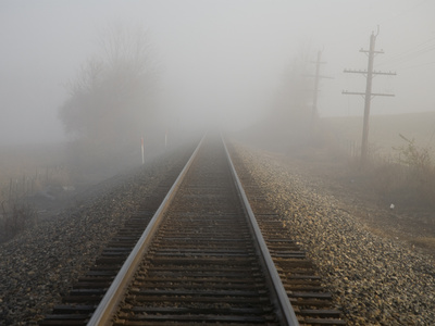 Railroad Tracks Stretch into Thick Fog in Early Morning Stretched Canvas Print