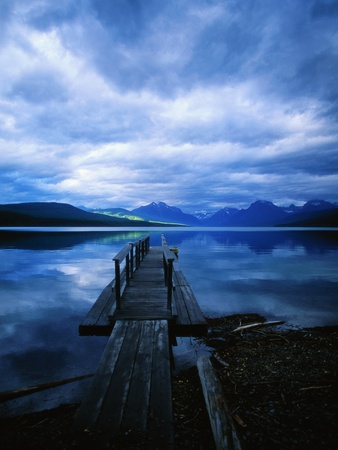 Pier at Lake McDonald Under Clouds Stretched Canvas Print