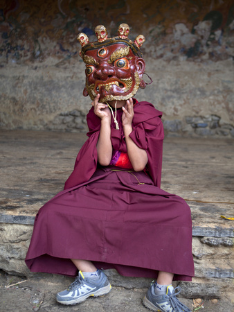Young Buddhist Monk Holding Traditional Carved Wooden Mask to His Face at the Tamshing Phala Choepa Stretched Canvas Print