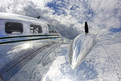 Clouds and Sky Reflecting Off the Shiny Silver Surface of An Airplane Stretched Canvas Print
