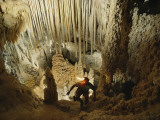 A spelunker explores a cave wearing a lanterned helmet