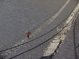 A Hunzukut Woman Crosses a Footbridge over the Hunza River