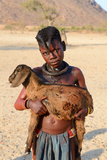 Himba Girl With Traditional Double Plait Hairstyle  Carrying A Goat