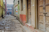 India  Varanasi a Man Walking Down a Stone Tiled Street in the Downtown Area