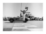 Man jumping waving checkered flag