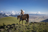 A Woman Rides the Range Above the Anderson Ranch to Deter Predators from the Cattle
