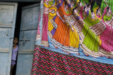 A Young Indian Boy Peeks Out of His Front Door  Partially Covered by a Tapestry