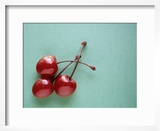 Three Cherries on a Green Background